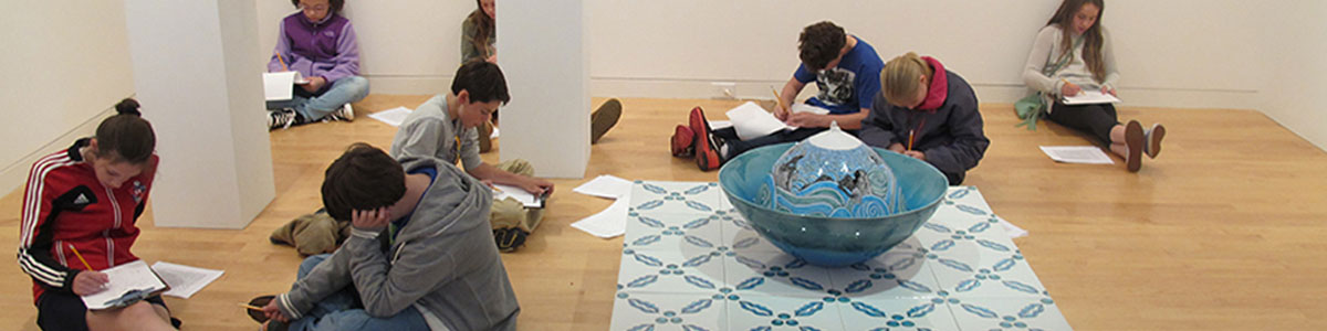 Group of students sit and work in the galleries at the Aldrich