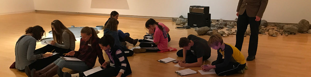 Group of students in the galleries at the Aldrich, writing